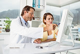 Doctor showing something on computer screen to patient