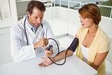Doctor checking blood pressure of woman at medical office