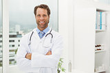 Smiling doctor with arms crossed in medical office