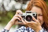 Pretty redhead taking a picture with retro camera