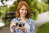 Smiling pretty redhead holding her camera