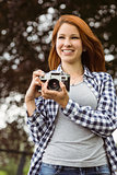 Woman wearing jeans and check shirt holding camera