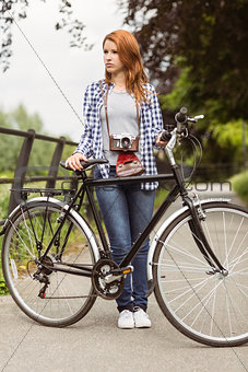 Beautiful redhead standing with bike