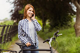 Smiling woman making a phone call in front of her bike