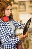 Redhead with a headphone around the neck holding a vinyl