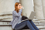 Woman drinking coffee and using laptop outside