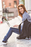 Portrait of a woman using her laptop and smiling at camera