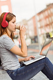 Girl using laptop, listening music and drinking coffee