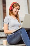 Happy enjoying woman listening with headphones to music