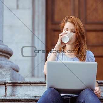 Beautiful woman drinking of disposable cup using her laptop