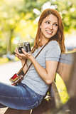 Redhead sitting on bench using her camera