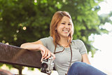 Smiling redhead sitting on bench holding her camera