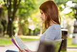 Cute redhead relaxing on bench and reading book