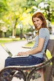 Redhead sitting on bench using laptop smiling at camera