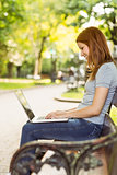 Woman sitting on park bench using laptop