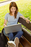 Happy girl sitting on bench using laptop