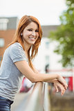 Redhead leaning on the bridge smiling at camera