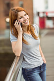 Smiling woman leaning on the bridge making a phone call