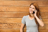 Cheerful redhead leaning against wall phoning