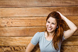 Happy beautiful redhead touching her hair