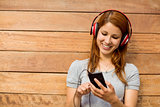 Girl listening music with headphones while sending message