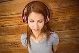 Peaceful redhead listening to music with closed eyes
