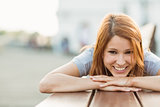 Smiling pretty redhead lying on bench on a sunny day
