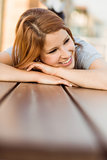 Smiling casual redhead lying on bench