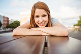 Portrait of a smiling redhead lying on bench
