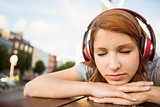 Woman listening with headphones to music with eyes closed