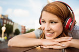 Pretty redhead lying on bench listening to music