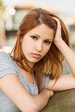 Sad redhead frowning at camera