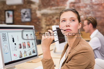 Thoughtful photo editor using computer in office