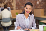Smiling businesswoman writing diary in office