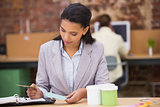 Businesswoman looking at diary in office
