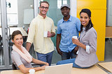 Colleagues with coffee cups during break at office