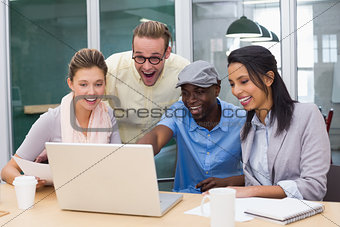Colleagues using laptop at office