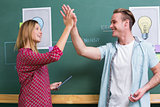 Creative business people high fiving by blackboard