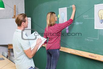 Creative business people at work against blackboard