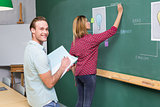 Creative business people at work against blackboard