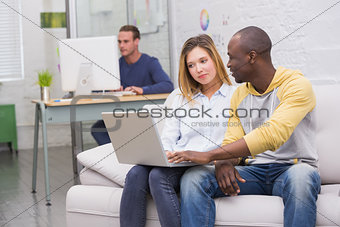 Casual colleagues using laptop on couch in office