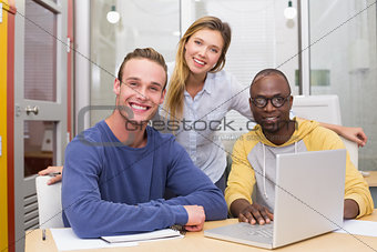 Creative colleagues using laptop in meeting
