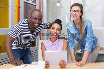 Smiling casual colleagues using digital tablet