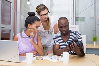 Photo editors looking at camera in office
