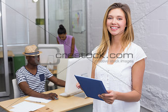 Casual woman with colleague using computer behind in office