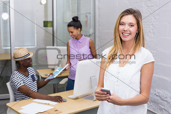 Casual woman with colleagues behind in office