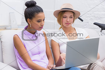 Casual business people using laptop on couch
