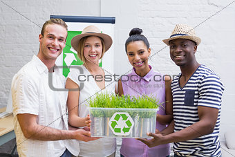 Creative business team holding plant with recycling symbol