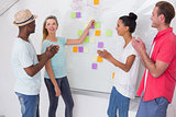 Creative team clapping hands by sticky notes on wall