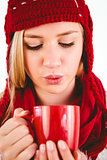 Festive blonde blowing over mug
